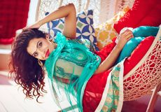 Härlig indisk kvinna i traditionell klänning som kopplar av på soffan Arkivfoto