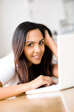 Härlig indisk kvinnadeltagare som hemma använder bärbar datordatoren Arkivfoto