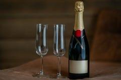 Härlig inomhus sikt av en champagneflaska med två exponeringsglas på en mockaskinntabell med mörk bakgrund fotografering för bildbyråer