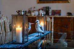 Härlig inre av ett rum med en tabell som står på de två stearinljusen och statyetterna av fåglar arkivbild