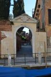 Härlig inre borggård som ses från den härliga lilla kanalen till och med en valvgång i Venedig Lopp ferier, arkitektur marsch royaltyfria foton