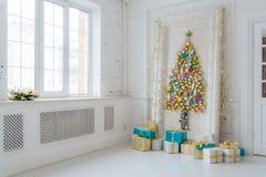 Härlig inre vardagsrum som dekoreras för jul Stor spegelram med ett träd som göras av bollar och leksaker Royaltyfria Bilder