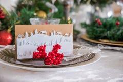 Härlig julferiebackround med röda prydnader, järnekbäret, pilbågen och julgarneringar i tappningstil arkivfoto