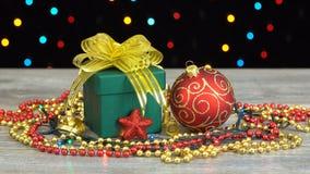 Härlig julgåvaask och garneringar på ett trägolv mot den färgrika blinkande girlanden på en svart bakgrund arkivfilmer
