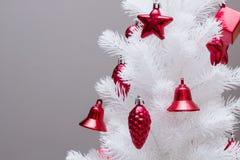 Härlig julgran med röda prydnader på grå bakgrund Royaltyfri Fotografi