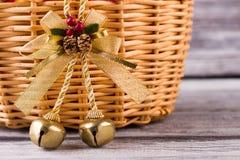 Härlig julklocka med kottar på en träkorg arkivfoton