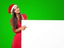 Härlig jultomten för flickan iin en hatt för hjälpreda är det hållande stora vita brädet Royaltyfri Fotografi