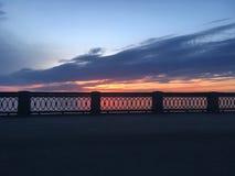 Härlig karmosinröd orange solnedgång på stranden, sikter av solen från balustraden Royaltyfri Foto