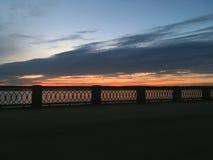 Härlig karmosinröd orange solnedgång på stranden, sikter av solen från balustraden Arkivbilder