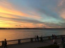 Härlig karmosinröd orange solnedgång på stranden, sikter av solen från balustraden Royaltyfri Fotografi