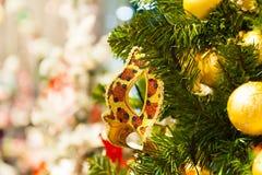 Härlig karnevalmaskering som hänger på julgranen i bakgrunden av ljusa Christmass garneringar Royaltyfria Bilder
