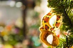 Härlig karnevalmaskering som hänger på julgranen i bakgrunden av ljusa Christmass garneringar Royaltyfri Fotografi