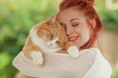 Härlig kel för ung kvinna med den gulliga röda katten arkivbilder