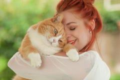 Härlig kel för ung kvinna med den gulliga röda katten royaltyfri foto