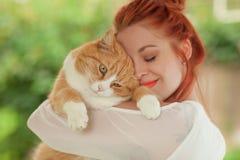 Härlig kel för ung kvinna med den gulliga röda katten arkivbild