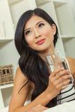 Härlig kinesisk asiatisk kvinna som dricker exponeringsglas av vatten Royaltyfria Foton