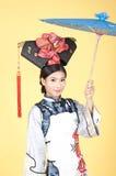 Härlig kinesisk kvinna som bär den traditionella dräkten mot gul bakgrund Royaltyfria Foton