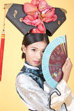 Härlig kinesisk kvinna som bär den traditionella dräkten mot gul bakgrund Royaltyfri Bild