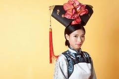 Härlig kinesisk kvinna som bär den traditionella dräkten mot gul bakgrund Arkivfoto