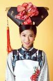 Härlig kinesisk kvinna som bär den traditionella dräkten mot gul bakgrund arkivbilder