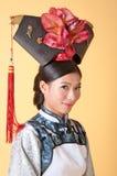 Härlig kinesisk kvinna som bär den traditionella dräkten mot gul bakgrund fotografering för bildbyråer