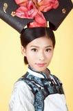 Härlig kinesisk kvinna som bär den traditionella dräkten mot gul bakgrund Arkivbild