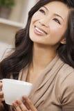 Härlig kinesisk orientalisk asiatisk kvinna som dricker te eller kaffe Arkivfoton