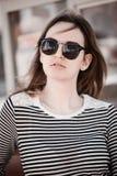 Härlig klänning för ung kvinna för brunett bärande, svarta cirkelexponeringsglas och gå på gatan som poserar nära den retro tappn Royaltyfria Foton
