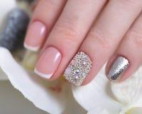 Härlig klassisk fransk manikyr med bergkristaller på den kvinnliga handen Närbild arkivfoto