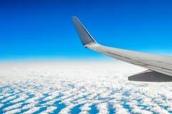 Härlig klassisk sikt av hyttventilen under ett flyg vid nivån, moln av blå himmel och jord Arkivbild