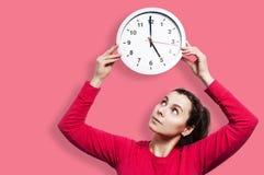 Härlig klocka för klocka för runda för brunettflickainnehav för objekttid för bakgrund begrepp isolerad white Den unga attraktiva Royaltyfri Bild