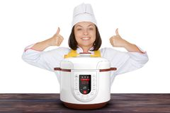 Härlig kock Show Thumbs Up för ung kvinna nära modern elkraft M Arkivbild