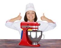 Härlig kock Show Thumbs Up för ung kvinna nära röd kökställning Royaltyfri Foto