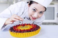 Härlig kock som dekorerar den läckra kakan Fotografering för Bildbyråer