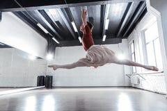 Härlig kompetent ballerina som gör splittringar i luften royaltyfria foton