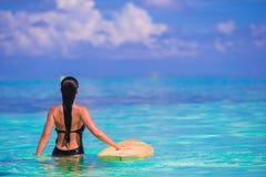 Härlig konditionsurfarekvinna som surfar under Arkivbild