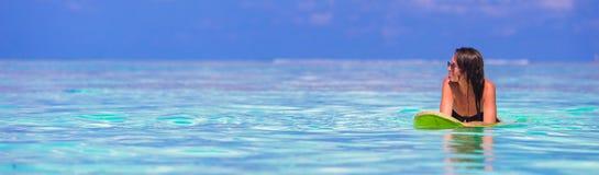 Härlig konditionsurfarekvinna som surfar under Arkivbilder