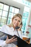 Härlig kontorsdam som talar på telefonen och kontrollerar profil Royaltyfri Bild