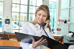 Härlig kontorsdam som talar på telefonen och kontrollerar profil Arkivbilder