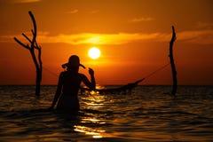 Härlig kontur för ung kvinna med gunga som poserar i havet på solnedgången, maldivian romantiskt landskap royaltyfri fotografi