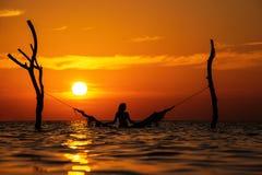 Härlig kontur för ung kvinna med gunga som poserar i havet på solnedgången, maldivian romantiskt landskap arkivbild