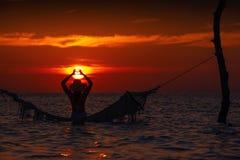 Härlig kontur för ung kvinna med gunga som poserar i havet på solnedgången, maldivian romantiskt landskap arkivbilder