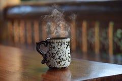 Härlig kopp kaffe med ånga på den wood tabellen Royaltyfri Fotografi