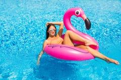 Härlig kvinna, bärande baddräkt som ligger på en rosa flamingoluftmadrass i en pöl av blått vatten, sommar arkivfoton