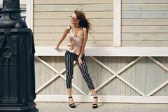 Härlig kvinna, bärande mörka exponeringsglas, mot bakgrunden av en trädvägg Modellen bär stilfull kläder, beiga Royaltyfri Bild