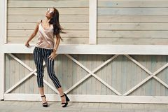 Härlig kvinna, bärande mörka exponeringsglas, mot bakgrunden av en trädvägg Modellen bär stilfull kläder, beiga Royaltyfri Foto