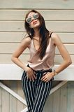 Härlig kvinna, bärande mörka exponeringsglas, mot bakgrunden av en trädvägg Modellen bär stilfull kläder, beiga Arkivfoto