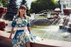 Härlig kvinna-brunett i sammanträde för blom- klänning nära fountaen Royaltyfri Fotografi