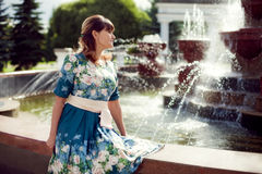 Härlig kvinna-brunett i sammanträde för blom- klänning nära fountaen Royaltyfria Bilder