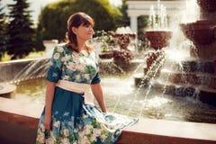 Härlig kvinna-brunett i sammanträde för blom- klänning nära fountaen Arkivbild